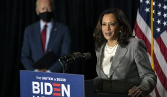 Democratic presidential candidate former Vice President Joe Biden stands left as his running mate Sen. Kamala Harris, D-Calif., speaks at the Hotel DuPont in Wilmington, Del., Thursday, Aug. 13, 2020. (AP Photo/Carolyn Kaster)