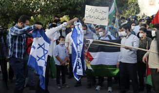 A group of protesters burn representations of Israeli flag during a gathering outside the United Arab Emirates' embassy in Tehran, Saturday, Aug. 15, 2020, to condemn the UAE's historic deal with Israel to open up diplomatic relations. (AP Photo/Ebrahim Noroozi)
