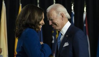 Democratic presidential candidate former Vice President Joe Biden and his running mate Sen. Kamala Harris, D-Calif., pass each other as Harris moves tot the podium. To speak during a campaign event at Alexis Dupont High School in Wilmington, Del. (AP Photo/Carolyn Kaster, File)