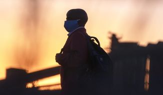 A man wearing protective masks to help curb the spread of the coronavirus walks back home from work in Germiston, near Johannesburg, South Africa, Thursday, Aug. 13, 2020. An Africa-wide study of antibodies to the coronavirus has begun, while evidence from a smaller study indicates that many more people have been infected than official numbers show, the Africa Centers for Disease Control and Prevention said Thursday. (AP Photo/Themba Hadebe)