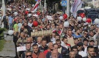 """Workers with handmade posters reading """"Go away!"""" march toward the Minsk Wheel Tractor Plant where Belarusian President Alexander Lukashenko addresses employees in Minsk, Belarus, Monday, Aug. 17, 2020. The top opposition candidate in Belarus' presidential vote who left the country last week announced Monday she was ready to """"act as a national leader"""" to help Belarus transition to a rerun of an election that extended the 26-year rule of authoritarian President Alexander Lukashenko and sparked unprecedented mass protests. (AP Photo/Dmitri Lovetsky)"""