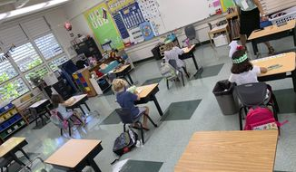 In this photo provided by Keoki Fraser, a small group of kindergarteners sits spaced apart in a classroom at Aikahi Elementary School in Kailua, Hawaii on Monday, Aug. 17, 2020. (Keoki Fraser via AP)