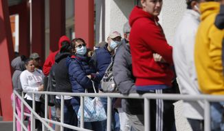 In this March 17, 2020, file photo, people wait in line for help with unemployment benefits at the One-Stop Career Center in Las Vegas. (AP Photo/John Locher, File)