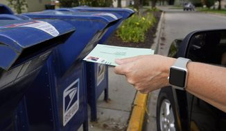 "In this file photo, a person drops into a mail box applications for mail-in ballots, in Omaha, Neb., Tuesday, Aug. 18, 2020. The Postmaster general announced Tuesday he is halting some operational changes to mail delivery that critics warned were causing widespread delays and could disrupt voting in the November election. Postmaster General Louis DeJoy said he would ""suspend"" his initiatives until after the election ""to avoid even the appearance of impact on election mail."" (AP Photo/Nati Harnik)  **FILE**"