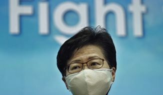 Hong Kong Chief Executive Carrie Lam listens to reporters questions during a news conference in Hong Kong, Tuesday, Aug. 18, 2020. (AP Photo/Vincent Yu)