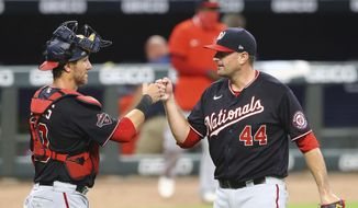 Washington Nationals closer Daniel Hudson and catcher Yan Gomes celebrate closing out the Atlanta Braves in the 9th inning in a  baseball game on Tuesday, Aug. 18, 2020, in Atlanta. (Curtis Compton/Atlanta Journal-Constitution via AP)