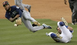 Seattle Mariners shortstop J.P. Crawford, left, tags out Los Angeles Dodgers' Chris Taylor, then throws to first to get Max Muncy for a double play during the seventh inning of a baseball game in Los Angeles, Tuesday, Aug. 18, 2020. (AP Photo/Alex Gallardo)