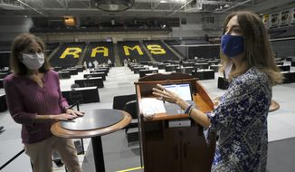 House Speaker Eileen Filler-Corn, D-Fairfax, right, and House Clerk Suzette Denslow, left, stand on the Speaker's podium inside the Siegel Center at VCU in Richmond, Virginia, Saturday, Aug. 15, 2020. The House of Delegates will meet in the space for a special session beginning on Tuesday instead of the House Chamber at the State Capitol to allow for social distancing during the COVID-19 crisis. (Bob Brown/Richmond Times-Dispatch via AP)
