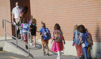 Students walk into Liberty Elementary School during the first day of class Monday, Aug. 17, 2020, in Murray, Utah. Murray City School District opened its doors offering its 6,300 students a choice among in-person learning, hybrid instruction and distance learning. (AP Photo/Rick Bowmer)
