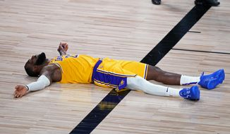 Los Angeles Lakers forward LeBron James (23) lies on the court after committing a foul during the second half of an NBA basketball game against the Portland Trail Blazers Tuesday, Aug. 18, 2020, in Lake Buena Vista, Fla. (AP Photo/Ashley Landis, Pool)  **FILE**