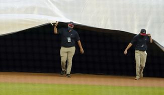 Members of the Atlanta Braves grounds crew cover the field ahead of a rain shower before the start of a baseball game between the Atlanta Braves and the Washington Nationals Wednesday, Aug. 19, 2020, in Atlanta. (AP Photo/John Bazemore)