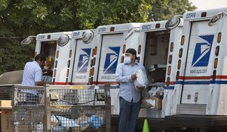 Postal workers load packages in their mail delivery vehicles at the Panorama City Post Office on Thursday, Aug. 20, 2020, in the Panorama City section of Los Angeles. (AP Photo/Richard Vogel)