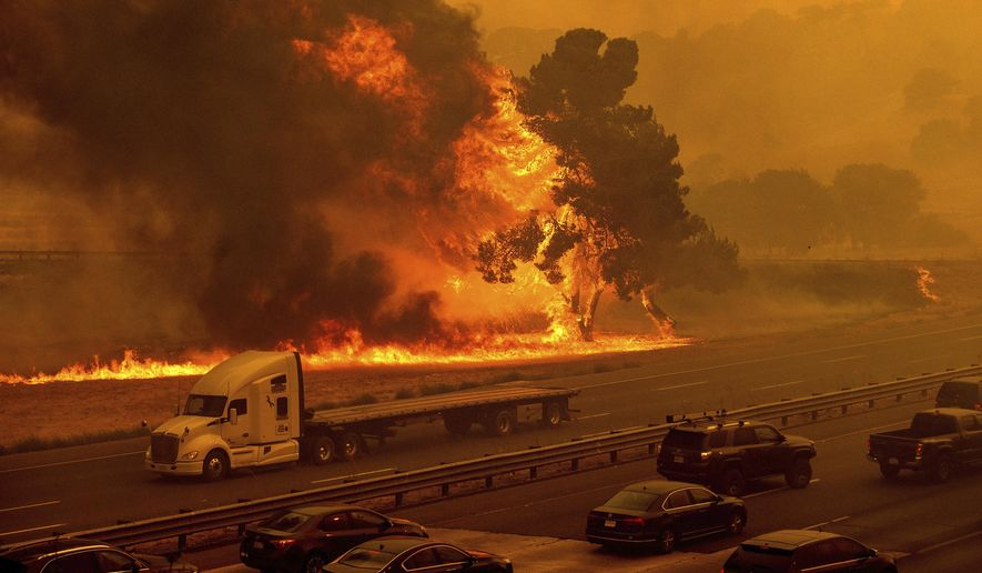 Flames from the LNU Lightning Complex fires jump Interstate 80 in Vacaville, Calif., Wednesday, Aug. 19, 2020. The highway was closed in both directions shortly afterward. Fire crews across the region scrambled to contain dozens of wildfires sparked by lightning strikes as a statewide heat wave continues. (AP Photo/Noah Berger)