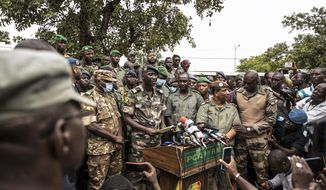 Colonel-Major Ismael Wague, center left, spokesman for the soldiers identifying themselves as the National Committee for the Salvation of the People, holds a press conference at Camp Soudiata in Kati, Mali, Wednesday, Aug. 19, 2020, a day after armed soldiers fired into the air outside President Ibrahim Boubacar Keita's home and took him into their custody. The Pentagon on Aug. 21 announced that it was cutting off military aid to the African country in response to the coup. (AP Photo)  **FILE**