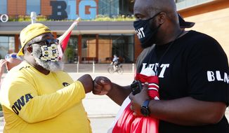 University of Iowa football players father Rodney Dixon, left, fist bumps Ohio State football players father Randy Wade outside Big Ten headquarters in Rosemont, Ill., Friday, Aug. 21, 2020. Parents of Big Ten football players, upset over the process that led to the postponement of the season until spring,  held a protest near the conference's Chicago-area headquarters Friday while an attorney in Nebraska demanded commissioner Kevin Warren turn over material illustrating how the decision was made. (Stacey Wescott/Chicago Tribune via AP)