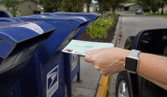 A person drops into a mailbox applications for mail-in ballots, in Omaha, Neb., Tuesday, Aug. 18, 2020.  (AP Photo/Nati Harnik)