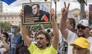 """A man holds a poster with a portrait of Alexei Navalny reading """"Navalny was poisoned, we know who is to blame, Alexei you must live"""" during an unsanctioned protest in support of Sergei Furgal, the governor of the Khabarovsk region, in Khabarovsk, 6,100 kilometers (3,800 miles) east of Moscow, Russia, Saturday, Aug. 22, 2020. Russian dissident Alexei Navalny, who is in a coma after a suspected poisoning, has arrived in Berlin on a special flight for treatment by specialists. (AP Photo/Igor Volkov)"""