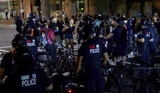 Protesters express themselves to Charlotte Mecklenburg Police bike officers at the intersection of Martin Luther King Jr. Blvd. and College Street in uptown Charlotte, N.C., on Friday, Aug. 21, 2020. (Jeff Siner/The Charlotte Observer via AP)