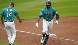 Seattle Mariners' Kyle Lewis, right, is congratulated by third base coach Manny Acta, left, while rounding the bases on a solo home run against the Texas Rangers in the second inning of a baseball game Friday, Aug. 21, 2020, in Seattle. (AP Photo/Elaine Thompson)