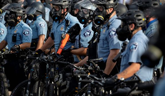 In this May 27, 2020, file photo, police gather en masse as protests continue at the Minneapolis 3rd Police Precinct in Minneapolis. More than 150 Minneapolis police officers have started the process of filing for disability claims since the death of George Floyd and the ensuing unrest in the city, with the majority citing post-traumatic stress disorder as the reason for their planned departure, according to an attorney representing the officers. (Carlos Gonzalez/Star Tribune via AP, File)
