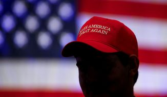 "Trump supporter wears a hat with the president's campaign slogan ""Make America Great Again."" (AP File Photo/Butch Dill)"