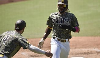 San Diego Padres' Wil Myers, left, congratulates Fernando Tatis Jr. for scoring a run off a double by Eric Hosmer during the fourth inning of a baseball game against the Houston Astros in San Diego, Sunday, Aug. 23, 2020. (AP Photo/Kelvin Kuo)