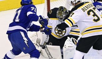 Boston Bruins goaltender Jaroslav Halak, second from left, makes a save against Tampa Bay Lightning center Anthony Cirelli (71) as Bruins' Patrice Bergeron (37) defends during first-period NHL Stanley Cup Eastern Conference playoff hockey game action in Toronto, Sunday, Aug. 23, 2020. (Frank Gunn/The Canadian Press via AP)