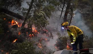 Ben Slaughter, a firefighter for the Boulder Creek Fire Department, stands on top of a fire truck along Highway 9 while monitoring flames from the CZU August Lightning Complex Fire, Saturday, Aug. 22, 2020, in Boulder Creek, Calif. (AP Photo/Marcio Jose Sanchez)