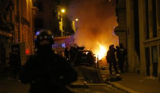 French police officers watch a car burning near the Champs-Elysee avenue following incidents after the Champions League soccer final match between PSG and Bayern Munich which is played in Lisbon, Portugal, Sunday Aug. 23, 2020 in Paris. Bayern Munich won 1-0. (AP Photo/Michel Euler)