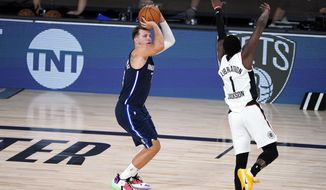 Dallas Mavericks' Luka Doncic (77) shoots his game-winning 3-point basket as Los Angeles Clippers' Reggie Jackson (1) defends during overtime of an NBA basketball first round playoff game Sunday, Aug. 23, 2020, in Lake Buena Vista, Fla. The Mavericks won 135-133 in overtime. (AP Photo/Ashley Landis, Pool)