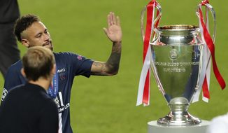 PSG's head coach Thomas Tuchel, left, watches as PSG's Neymar touches the trophy for winners of the Champions League final soccer match between Paris Saint-Germain and Bayern Munich at the Luz stadium in Lisbon, Portugal, Sunday, Aug. 23, 2020. (Miguel A. Lopes/Pool via AP)