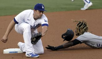 Colorado Rockies' Raimel Tapia, right, steals second base as Los Angeles Dodgers shortstop Corey Seager catches the ball, but cannot apply the tag in time during the first inning of a baseball game in Los Angeles, Saturday, Aug. 22, 2020. (AP Photo/Alex Gallardo)