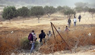 Palestinian laborers cross illegally into Israel from the West Bank through an opening in a fence near the West Bank town of Hebron, Sunday, Aug. 23, 2020. (AP Photo/Mahmoud Illean)