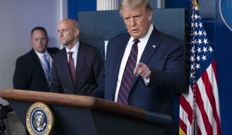President Donald Trump speaks, accompanied by Food and Drug Administration Commissioner Dr. Stephen Hahn, center, during a media briefing in the James Brady Briefing Room of the White House, Sunday, Aug. 23, 2020, in Washington.(AP Photo/Alex Brandon)