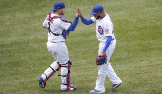 Chicago Cubs relief pitcher Jeremy Jeffress, right, celebrates with catcher Victor Caratini, left, after delivering final out against the Chicago White Sox during the ninth inning of a baseball game, Sunday, Aug. 23, 2020, in Chicago. (AP Photo/Kamil Krzaczynski)