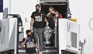 Bayern goalkeeper Manuel Neuer carries the trophy during the arrival of the FC Bayern Munich team at Munich Airport, Germany, after their victory in the Champions League final against PSG, Monday, Aug. 24, 2020. (Peter Kneffel/Pool via AP)