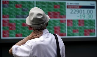 A man looks at an electronic stock board showing Japan's Nikkei 225 index at a securities firm in Tokyo Monday, Aug. 24, 2020. Asian stock markets rose Monday after Wall Street hit a new high despite lingering unease about a possible second wave of coronavirus infections.  (AP Photo/Eugene Hoshiko)