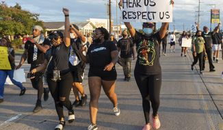 Protesters march down Amb Caffery and Johnston St. Sunday, Aug. 23, 2020, in Lafayette, La.  (Scott Clause/The Daily Advertiser via AP)