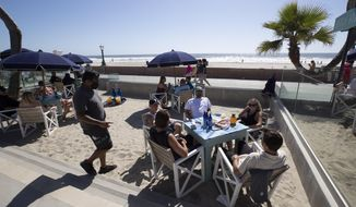 FILE - In this May 21, 2020 file photo People sit at tables at the Beach House Grill in San Diego. As California faces multiple crises, encouraging signs are starting to emerge in the coronavirus fight. Two of the state's three most populous counties are now off a statewide monitoring list, meaning they could be eligible to open schools within weeks, and Gov. Gavin Newsom indicated guidelines for reopening businesses and other sectors of the economy will be out this week. (AP Photo/Gregory Bull, File)