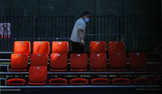 A worker wearing a face mask to help curb the spread of the coronavirus cleans the seats at a basketball court in Beijing, Monday, Aug. 24, 2020. China has gone eight days without reporting a new local case of COVID-19, with the Beijing International Film Festival among public events that are returning. (AP Photo/Andy Wong)