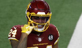 华盛顿足球队 running back Antonio Gibson (24) points to his mouth as he celebrates his touchdown in the second half of an NFL football game against the Dallas Cowboys in Arlington, Texas, Thursday, Nov. 26, 2020. (AP Photo/Roger Steinman)
