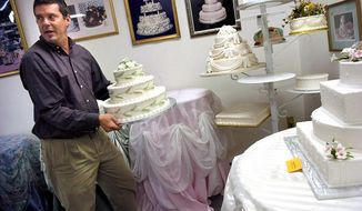 Creative Cakes owner Spencer Biles, carrying one of his creations into the Silver Spring company's display room, faces a daunting demand for cakes for Saturday, considered the most auspicious wedding date in decades.