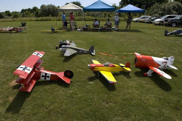 ** FILE ** Replicas of a World War I-era Fokker DR-1 triplane (left), a stunt plane, the Granville Brothers' Gee Bee racing plane and a World War II-era DeHavilland Mosquito (background) wait to take to the air as members of the Freestate Aeromodelers fly scale reproductions of historic aircraft during the third annual Airplanes of the World Scale Fly-In at Konterra Model Airpark in Laurel, Md., on Saturday, June 23, 2007. ( J.M. Eddins Jr./The Washington Times)