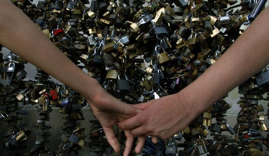 A couple hold hands in front of a local spectacle, a fence where lovers place their locks in Pecs.