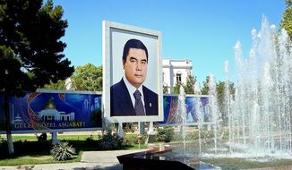 ** FILE ** Following the lead of his predecessor, Turkmenistan's new president, Gurbanguly Berdymukhamedov, made sure in 2007 that his countrymen knew who he was, with portraits springing up everywhere, such as this one next to a fountain in the capital, Ashgabat. (Joshua Kucera/The Washington Times)
