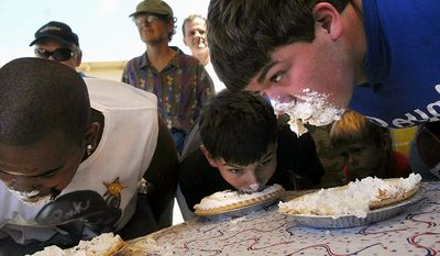 Christian Kersey (left), David Sabre (center) and Pablo Piggott race to finish their pies during a pie-eating contest at the Fauquier County Fair in Warrenton, Va., Saturday, July 21, 2007. (Rod Lamkey, Jr./The Washington Times)