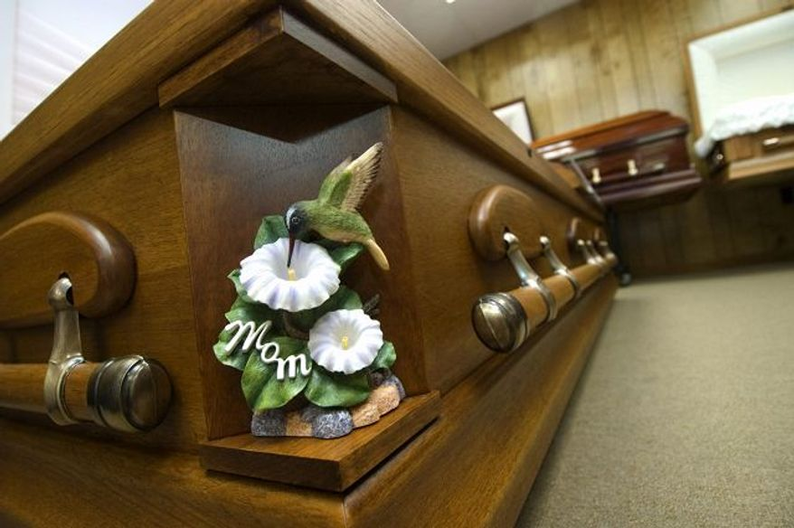 A casket at Keeney and Basford Funeral Home in Frederick, Md., displayed a decorative symbol. Casket can have the standard corners replaced with a variety of pieces, allowing families to create a casket that is more about personality than tradition.