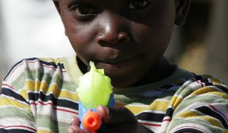 ** File ** A child in Johannesburg plays with a water pistol.
