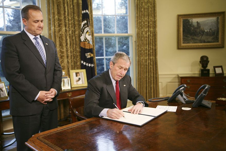 WASHINGTON - JANUARY 29: U.S. President George W. Bush signs the Executive Order Protecting American Taxpayers from Government Spending on Wasteful Earmarks as Jim Nussle, Director Office of Management and Budget, looks on in the Oval Office of the White House January 29, 2008 in Washington, DC. (Photo by Dennis Brack-Pool/Getty Images)