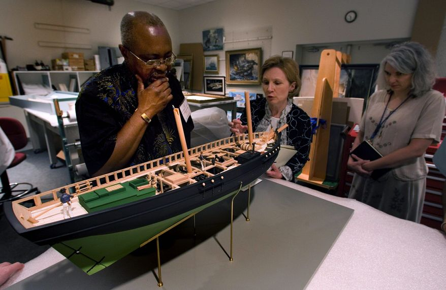 Simao Souindoula studies a scale model of a slave ship in Colonial Williamsburg with Priscilla Hauger, director of exhibitions. He visited several historical sites in Virginia to network for his museum in Angola, the National Museum of Slavery, as he seeks to deepen U.S. ties with his country beyond trade. (Associated Press)